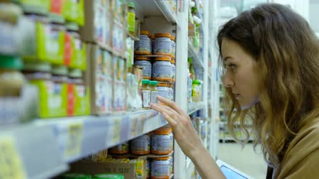 dyes : Young woman with a tablet carefully examines the composition of baby food in a supermarket