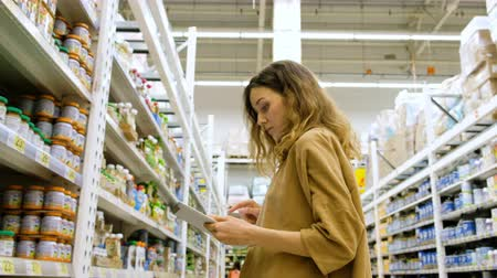 dyes : Young woman with a tablet picks food in a supermarket