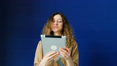 dependência : Young woman greets friends on a tablet by video link on a blue wall background Vídeos