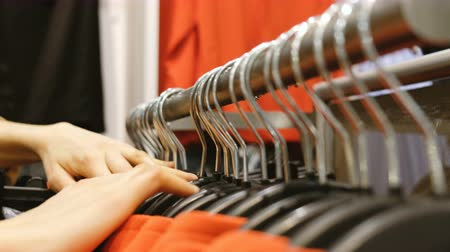 tomar : Woman takes clothes on a hanger in a store, close-up