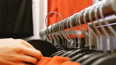 vállfa : Woman returns clothes to a hanger in a store, close-up Stock mozgókép