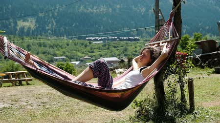 растягивается : Girl sleeping in a hammock on the nature against the background of green mountains, slow motion