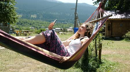 растягивается : Woman is resting and swinging in a hammock and using the phone in nature Стоковые видеозаписи