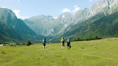 кемпинг : Tourists hikers with large backpacks are walking in the mountains in a hike against the backdrop of a beautiful landscape.