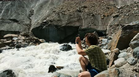 góral : Man photographs on a smartphone landscape - mountain river, a glacier Wideo