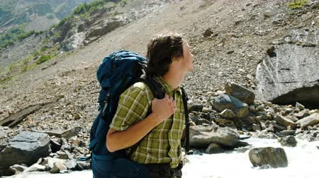 альпинизм : Tourist stands with a backpack near a fast river and looks at the mountains