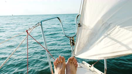 луки : Male feet on the bow of a sailing yacht closeup in the open sea