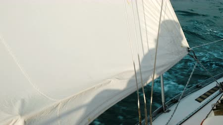 elite : Shadow on the sail of a yacht in close up swinging on the waves in the sea