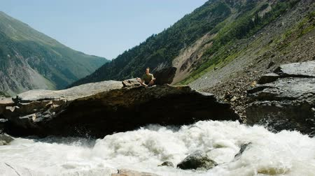 глыба : Man sits in a lotus position and meditates in mountains. River flows fast