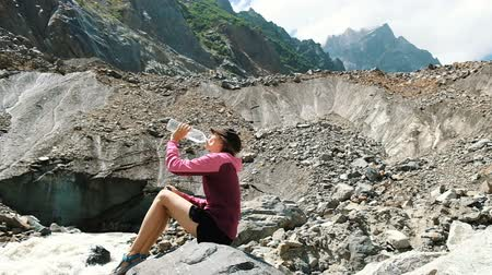 isteyen : Girl tourist drinks water from a bottle in the mountains, slow motion Stok Video