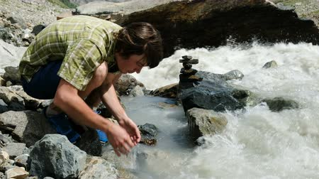 naživu : Man tourist drinks water from the palms of a mountain river close up