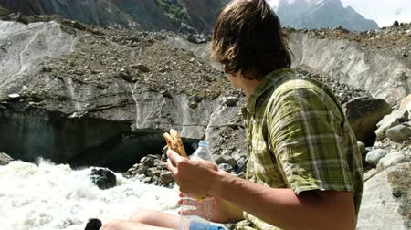 закалки : Man tourist drinks water and eats bread in the mountains close up Стоковые видеозаписи