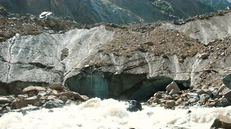 çöküş : Rockfall on a hot day. Mountain river flows out from under the glacier