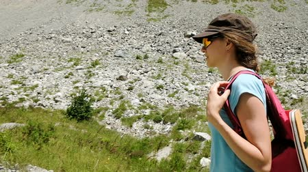 podmínky : Girl tourist walks with backpack in the mountains slow motion Dostupné videozáznamy