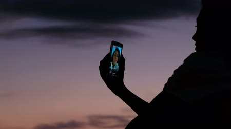 szépen : Silhouette of a girl uses a cellphone to live on social networks at sunset close-up