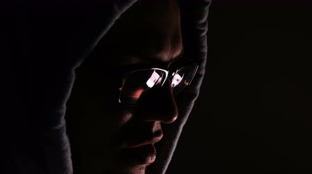 kraker : Hacker in glasses and a hood works at a computer in the dark, a reflection in glasses close-up, 4k