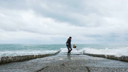 mooring : Joyful man running away from the big waves on the dock, slow motion Stock Footage