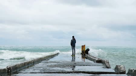 moorage : A man tries to escape from the big waves on the dock, slow motion
