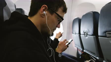 meio : A man listens to music on headphones and uses a telephone in an airplane Stock Footage
