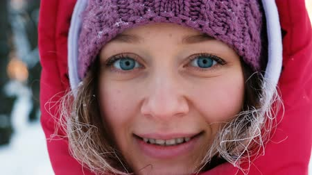 into the camera : Portrait of beautiful girl with blue eyes smiling camera close-up, hair in frost from cold, 4k Stock Footage