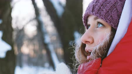 warms : A beautiful girl is basking in the frost and letting steam from her mouth close up, 4k Stock Footage
