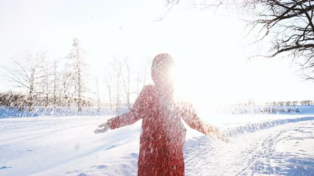 throws : Girl throws snow in winter at sunset, the snow shines in the sun, slow motion Stock Footage