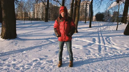 минус : The man freezes in the park in winter, shifts from foot to foot, slow motion Стоковые видеозаписи