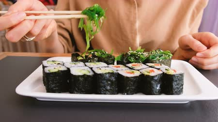nori : The girl eats seaweed with chopsticks in a Japanese restaurant
