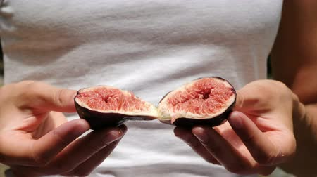 entrails : Woman holds figs in half open closeup in nature in summer