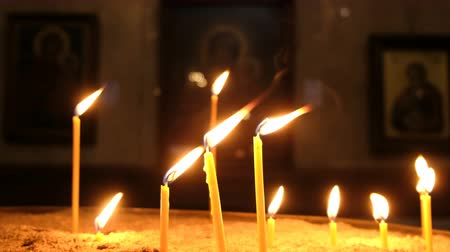 stained glass : Candles are burns and standing in the sand in candlestick in an Orthodox church