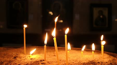 stained glass : Candles are burning in the old Christian church, slow motion Stock Footage
