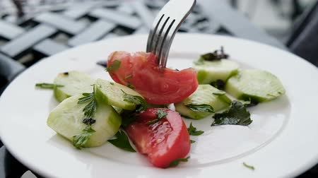 domates : Fork pierces a tomato and cucumber salad on a white plate close-up, slow motion Stok Video