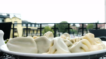основное блюдо : Hot steaming khinkali dumplings are lying on a white plate in an outdoor restaurant close up