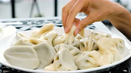 gürcü : Woman takes khinkali, a large portion of dumplings, hand in restaurant close-up Stok Video