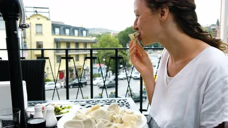 клецка : Young beautiful woman eating khinkali or dumplings with hands in a restaurant