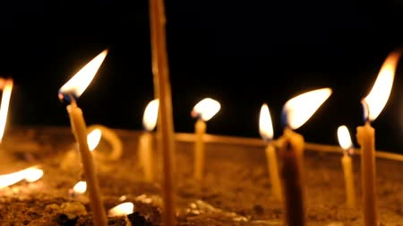 bereavement : Wax candles burn in the dark in church against dark background close-up camera movement, slow motion