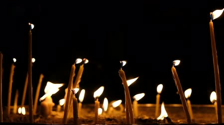 stained glass : Wax candles burn in the dark in church against dark background, slow motion