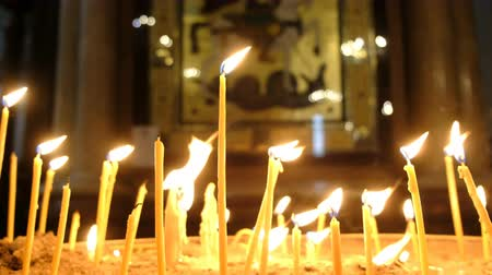 stained glass : Wax candles burn in the dark in the Orthodox Church framed with an ancient icon
