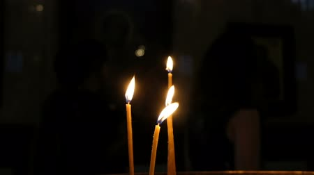 bereavement : Four candles burning in the church in the dark against the background of people, slow motion Stock Footage