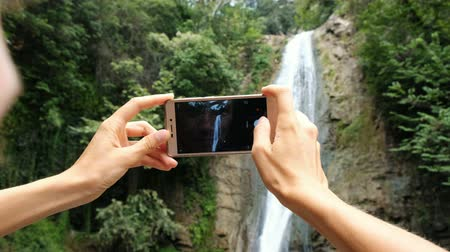 dinlenmek : Woman focuses on the phone screen and takes a photo of the waterfall close-up