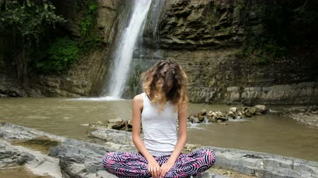 tilts : Woman is sitting in the lotus position and doing exercises on the background of a large waterfall