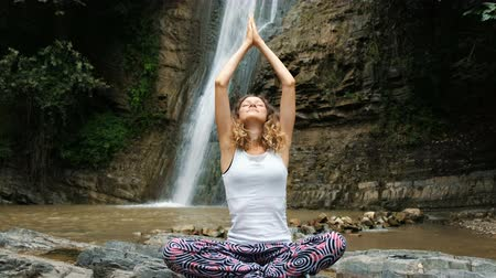 tilts : Woman sits in a lotus position and folds her hands in a namaste pose against of a large waterfall.