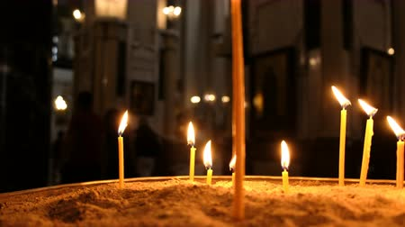 bereavement : Defocus candles are burns and standing in the sand in candlestick in an Orthodox church