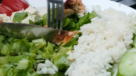 chicken pieces : Knife cuts chicken kebab close-up on a plate with salad and rice