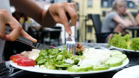 villa : Girl cuts chicken kebab close-up and string the kebab on a fork with salad