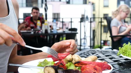 dietético : Woman eats grilled vegetables with a fork close up against the backdrop of visitors Stock Footage