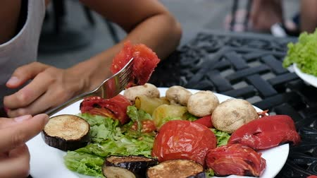 dietético : Woman eats roasted tomato with a fork, grilled vegetables close-up, slow motion