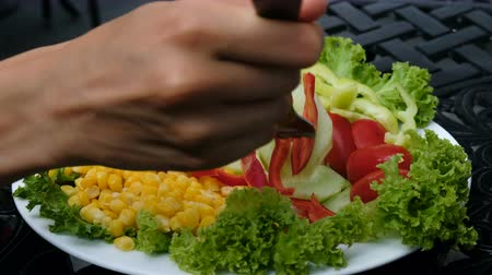 cuketa : Woman takes a fork with fresh pepper, cucumber and tomato with vegetable plate close-up Dostupné videozáznamy