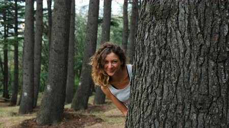 embarrassed : Girl looks out from behind a tree and smiles Stock Footage