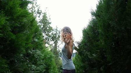 enjoys : Happy woman spinning around herself among spruce and fluffy bushes, slow motion Stock Footage